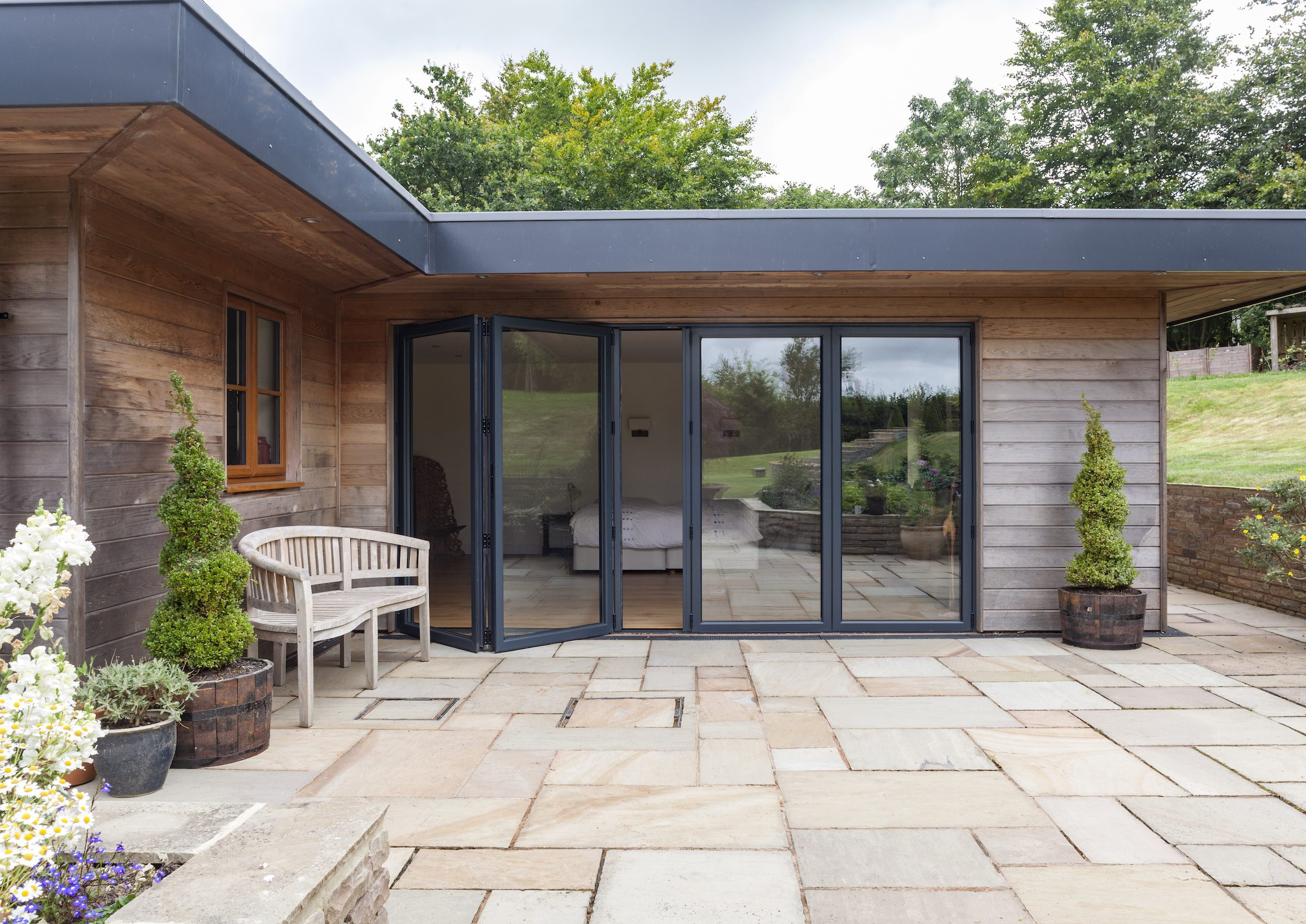 smart systems bifold doors showing the visofold bifold doors 6000 model in a modern extension with wood cladding