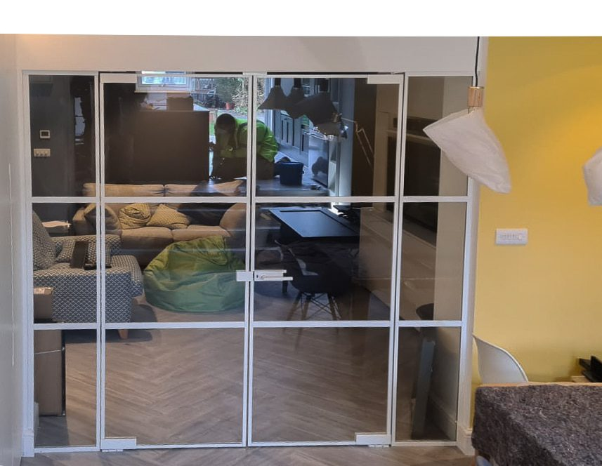 internal steel look doors and screens separating a lounge and kitchen